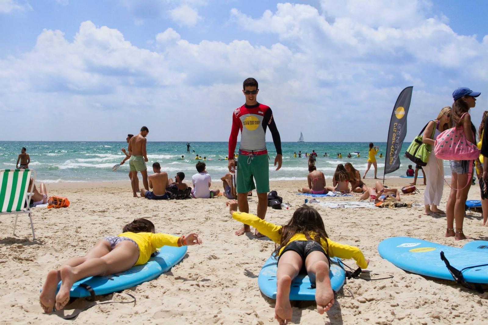 תמונה של הים בחוף הצוק תל אביב, עם הלוגו של קייטנת הגלישה סי אנד סאן סרף