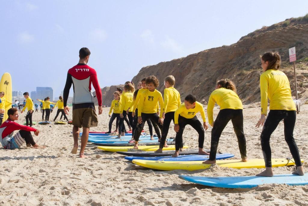 ילדים עומדים על גלשן מתחילים במסגרת שיעור גלישה בקייטנת גלישה בסי אנד סאן