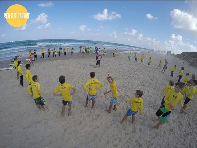 מעגל ילדים המבצעים תרגילי חימום לפני הכניסה לגלישה בים