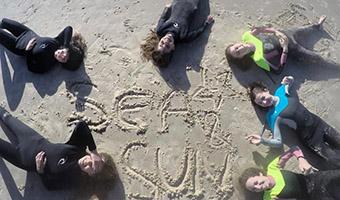 ילדים שוכבים על חוף הים במעגל, במרכז המעגל סמל קייטנת הגלישה בחוף הצוק תלן אביב