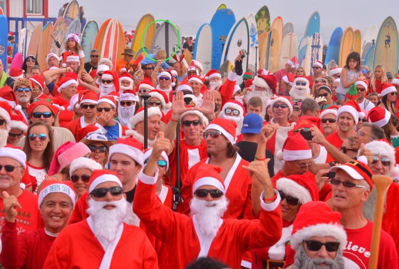 מאוד גולשים בתחפושת סנטה קלאוז מתכוננים לכניסה למים עם גלשני גלים. כחלק ממסורת