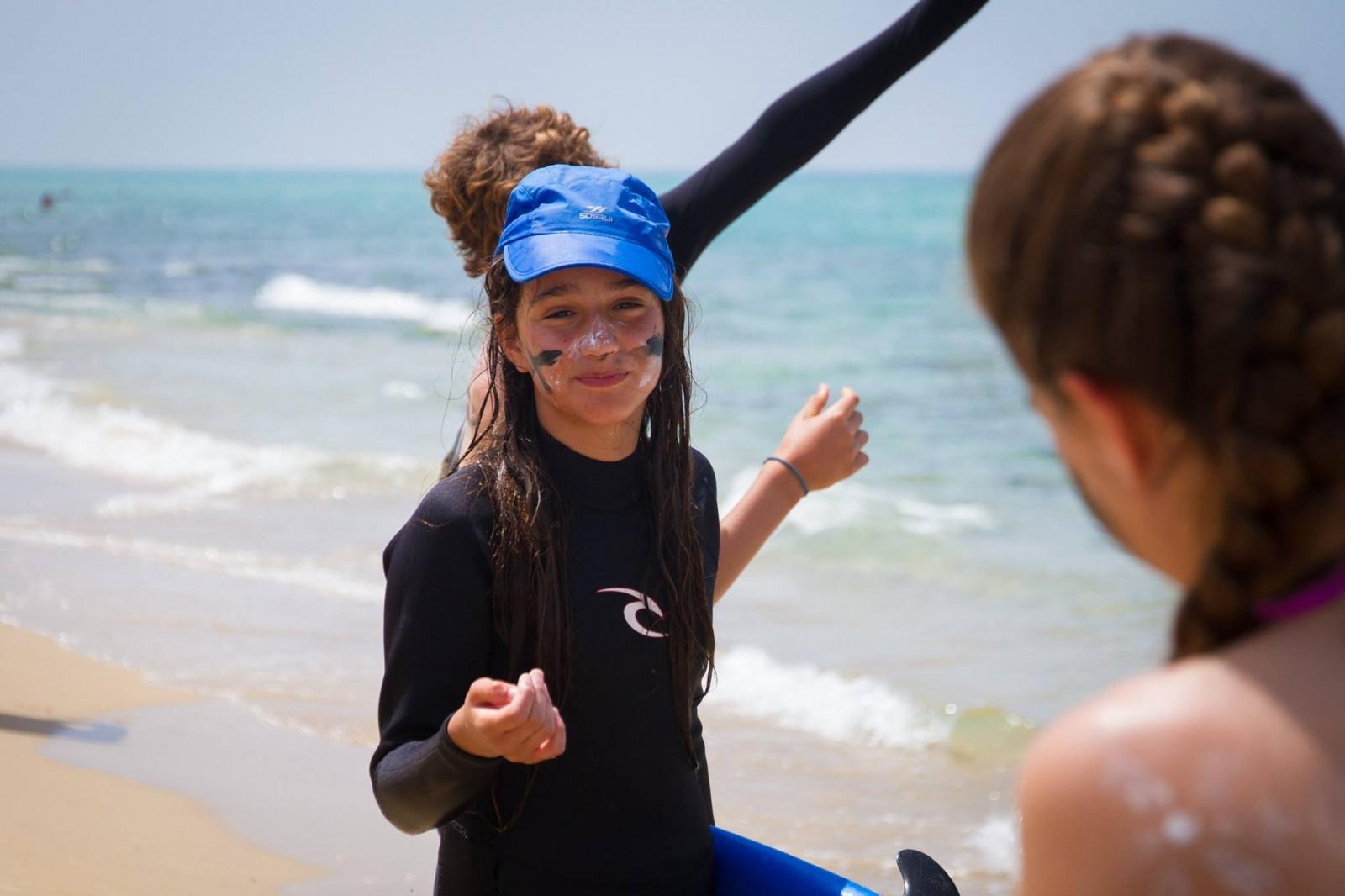 ילדה במחנה הגלישה פסח, מרוחה בקרם הגנה על הפנים וכובע קייטנה כחול לראשה